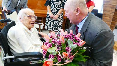 Pani Konstancja Wróbel odbiera kwiaty od wicewojewody śląskiego. Fot. Śląski Urząd Wojewódzki.