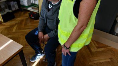 Podejrzany siedzi na krześle z rękami zakutymi w kajdanki, widoczna również policjantka (fot.KWP Katowice)