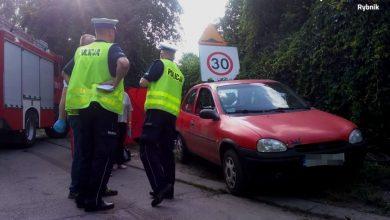 Na zdjęciu czerwony Opel Corsa, oraz policjanci zabezpieczający miejsce wypadku, w którym w Rybniku-Kamieniu zginął 7-letni chłopiec