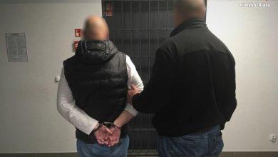 Zatrzymany 38-latek prowadzony przez funkcjonariusza policji do aresztu. [fot. Śląska Policja]