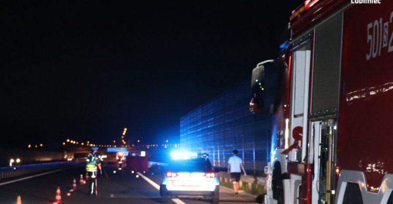 Na zdjęciu miejsce wypadku na autostradzie A1 , widoczny policyjny radiowóz na sygnale, policjant w trakcie czynności i wóz strażacki