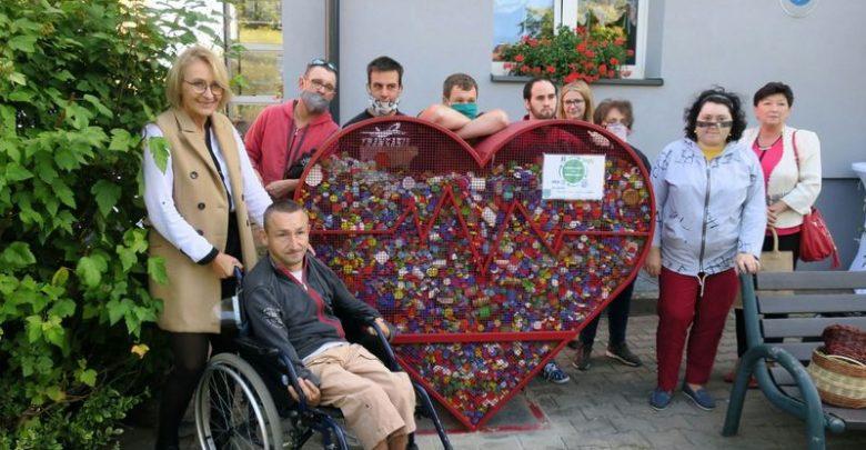 Czerwone metalowe serce na plastikowe nakrętki. Obok uczestnicy i pracownicy Warsztatów Terapii Zajęciowej. Fot. L. Tyl/UM Rybnik