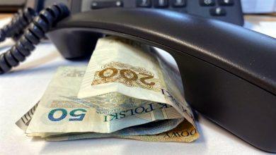 słuchawka telefonu leży na stoliku przy niej banknoty pieniędzy, w tle telefon z klawiaturą