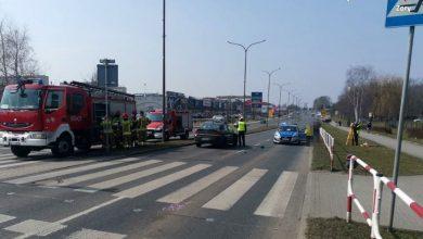 Zdjęcie z miejsca wypadku, na pierwszym planie oznakowane przejście dla pieszych, w tle radiowóz, policjanci, wóz strażacki i strażacy