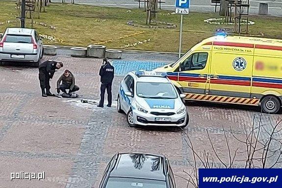 Miejsce zdarzenia. Stojący na placu policjanci obok radiowozu i karetki